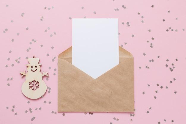 Carta de envelope de papel kraft com maquete de cartão branco em branco sobre fundo rosa com estrelas de confete.