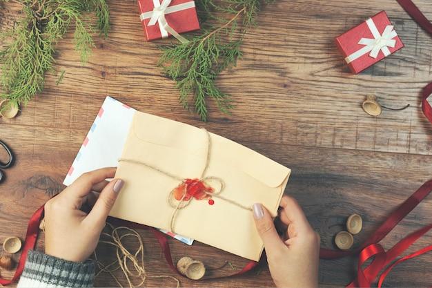 Carta de mão de mulher com itens cristmas na mesa