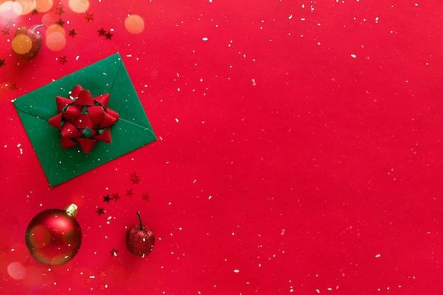 Carta de natal com galhos de árvores de natal, enfeites, enfeites de brilho na superfície vermelha. postura plana, banner, cópia espaço