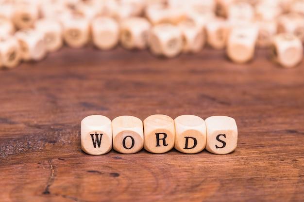 Carta de palavras feita com cubos de madeira sobre a mesa marrom