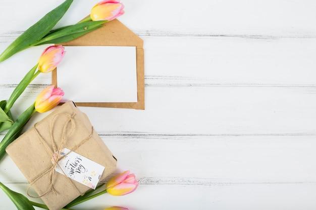 Carta de quadro com caixa de presente de dia das mães e flores