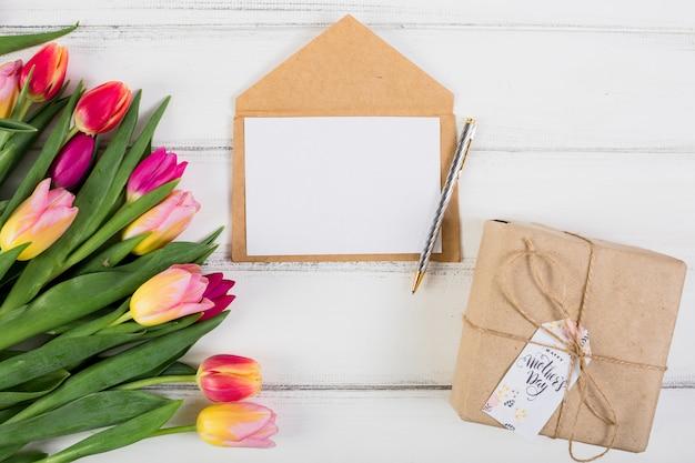 Carta de quadro em torno da caixa de presente e tulipas