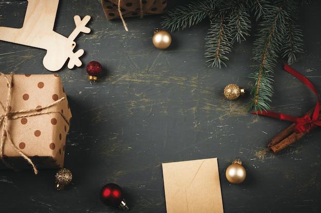 Carta de saudação, envelope e penas rodeado de decorações de natal