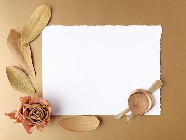 Carta em branco e rosas secas em um fundo dourado