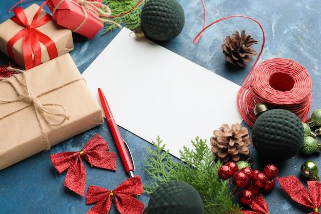 Carta em branco para o papai noel e decoração de natal em concreto azul, vista superior