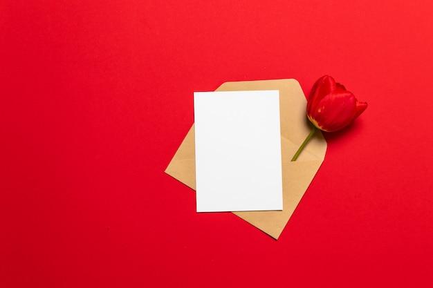 Carta, envelope em papel de eco e tulipa vermelha em fundo. namorados