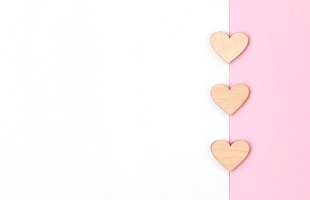 Carta ou cartão com corações de madeira na mesa rosa pastel