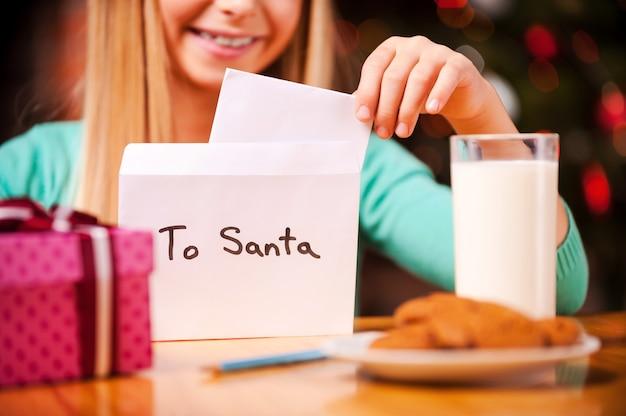 Carta para o papai noel. close-up de uma menina alegre colocando uma carta para o papai noel dentro do envelope, enquanto está sentado à mesa com um copo de leite e biscoitos colocados sobre ele