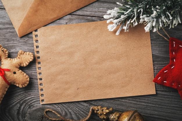 Carta para o papai noel, decorações de natal e uma folha de papel em branco para o texto em uma mesa de madeira