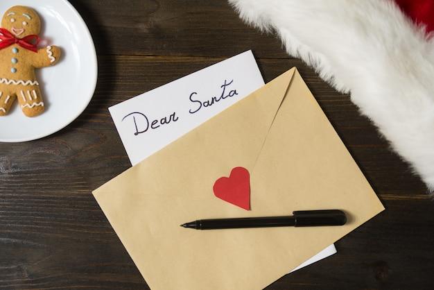 Carta para o papai noel em um envelope, caneta e pão de gengibre