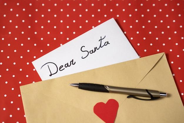 Carta para o papai noel em um envelope. caneta, superfície vermelha. conceito de natal e ano novo