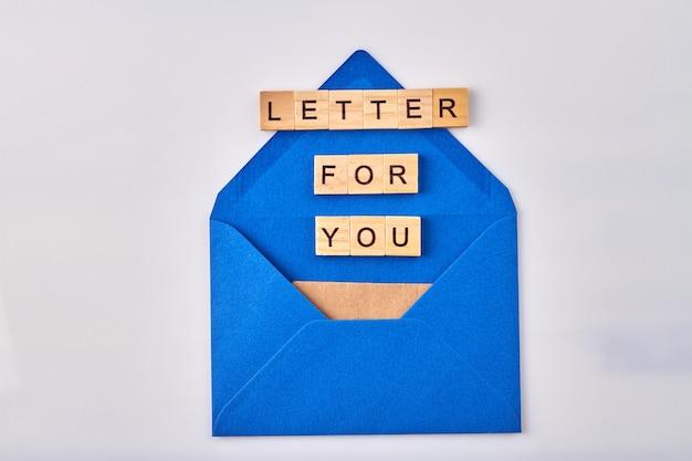 Carta para você. blocos de madeira em tiro vertical de envelope azul.
