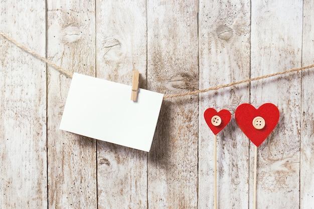 Carta pendurado em uma corda e dois corações vermelhos
