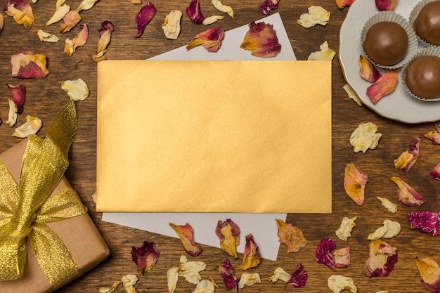 Carta perto de placa com doces e caixa de presente entre folhas secas