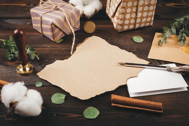 Carta vazia com uma pena no fundo de madeira velha, decorada com objetos de natal