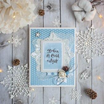 Cartão artesanal de inverno sobre o fundo de madeira com flocos de neve, algodão, cones e guirlanda