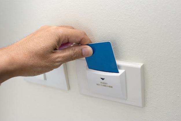 Cartão asiático da posse da mão do homem para o cartão chave da exploração do controle de acesso da porta para travar e destravar a porta