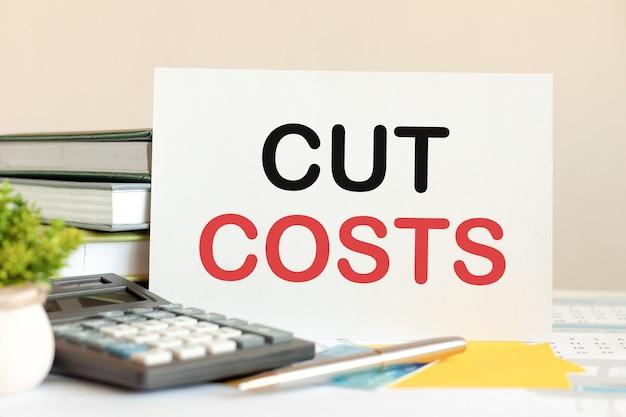 Cartão branco com redução de custos de texto fica em cima da mesa contra livros empilhados, calculadora, caneta, planta em vaso verde. conceito de negócios e financeiro. foco seletivo.
