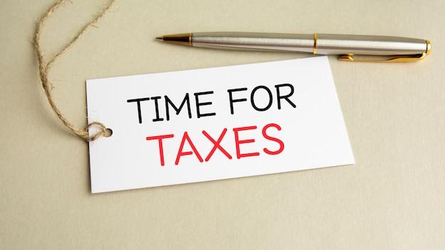 Cartão branco com tempo de texto para impostos com caneta de metal em fundo cinza.