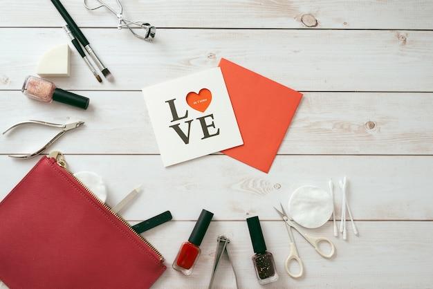Cartão branco com um padrão em forma de coração, conjunto de manicure e esmalte em fundo de madeira. dia dos namorados. flatlay