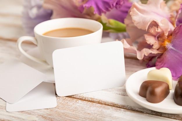 Cartão branco com uma xícara de café, bombons de chocolate e flores de íris em fundo branco.