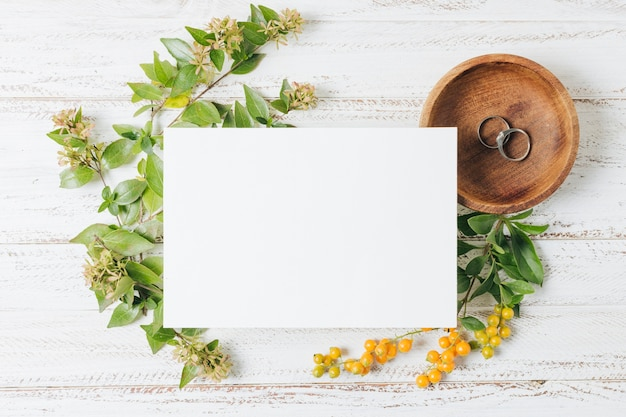 Cartão branco de casamento sobre os anéis; flores e bagas amarelas na mesa de madeira branca