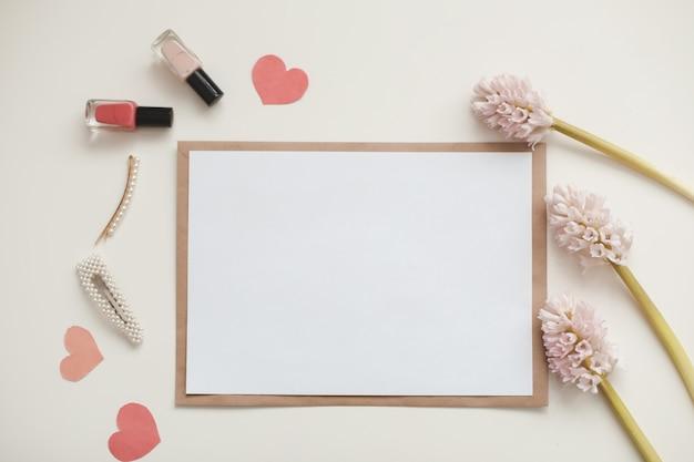 Cartão branco de maquete e envelope com flores no fundo