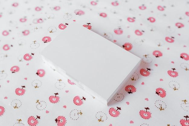 Cartão branco de negócios sobre fundo bonito floral textil