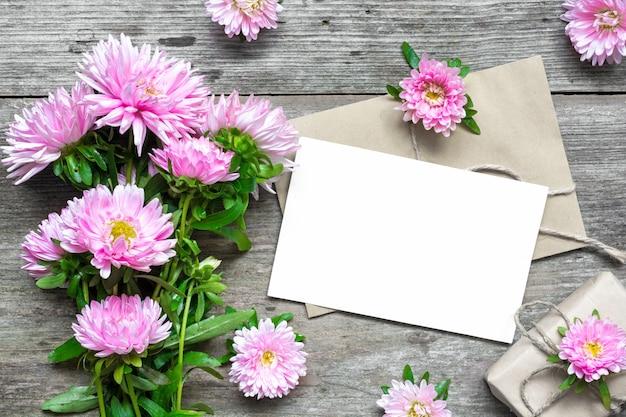 Cartão branco em branco com buquê de flores de áster rosa e envelope com botões de flores e caixa de presente