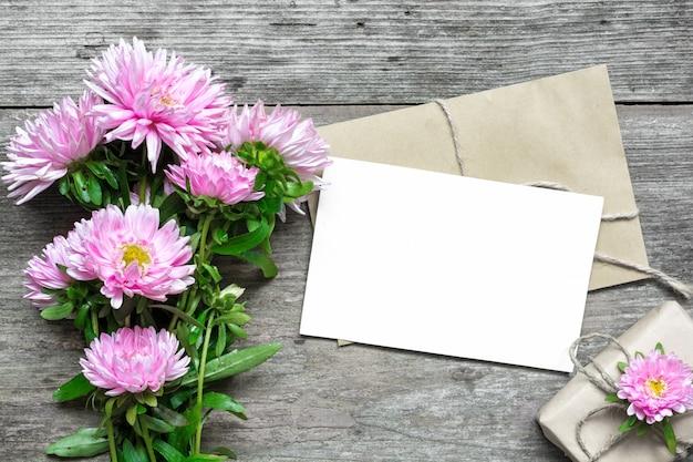 Cartão branco em branco com buquê de flores de áster rosa e envelope com caixa de presente