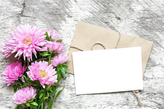Cartão branco em branco com buquê de flores de áster rosa e envelope