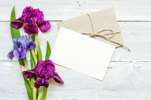 Cartão branco em branco com buquê de flores de íris roxo e azul e envelope