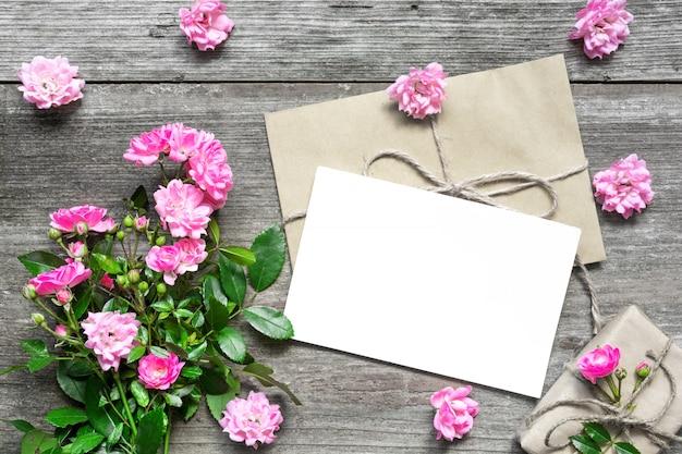 Cartão branco em branco com buquê de flores rosa e envelope com botões de flores e caixa de presente