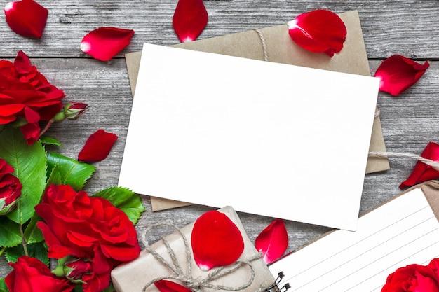 Cartão branco em branco com buquê de flores rosas vermelhas e envelope com pétalas, caderno pautado e caixa de presente