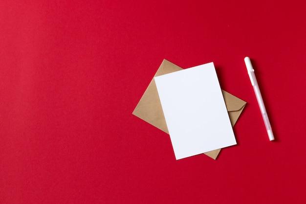 Cartão branco em branco com caneta. folha de papel branco vazio isolada no fundo vermelho