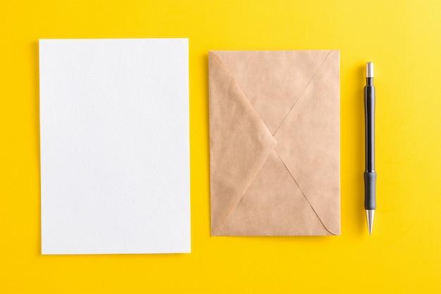 Cartão branco em branco com envelope de papel pardo kraft e lápis amarelo