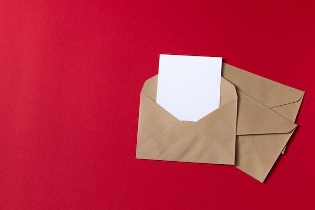 Cartão branco em branco com kraft papel marrom envelope modelo simulado acima