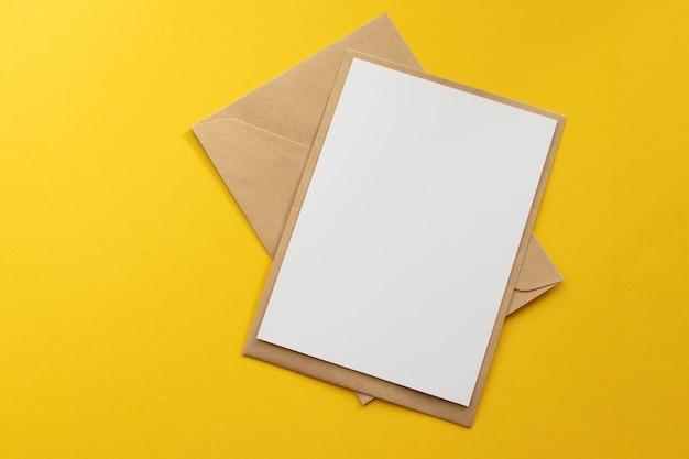 Cartão branco em branco com modelo de envelope de papel marrom kraft simulado acima sobre fundo amarelo