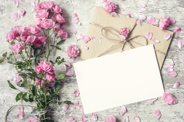 Cartão branco em branco e envelope com flores rosas rosa