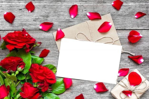 Cartão branco em branco e envelope com flores rosas vermelhas, pétalas e caixa de presente
