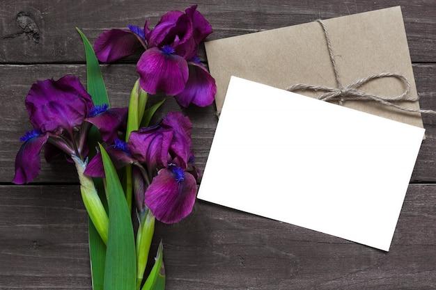 Cartão branco em branco e envelope com maquete de flores de íris roxo no fundo escuro de madeira rústico