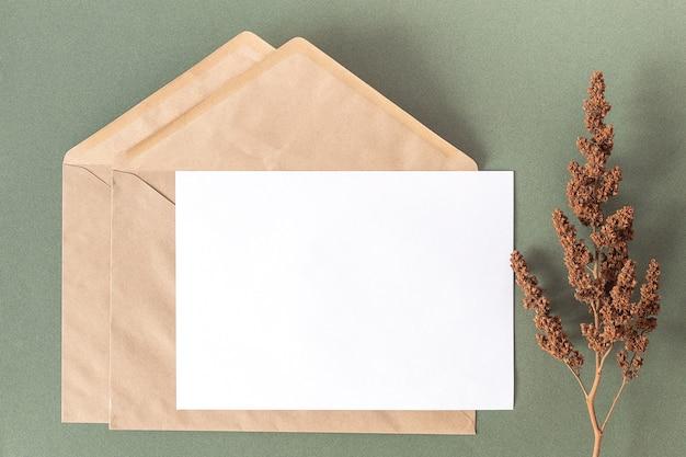 Cartão branco em branco, envelope artesanal e planta de flores secas no verde