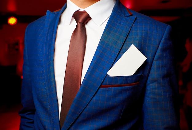 Cartão branco em branco no bolso de uma jaqueta azul masculina