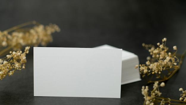 Cartão branco mock up e modelo com a flor em fundo preto.