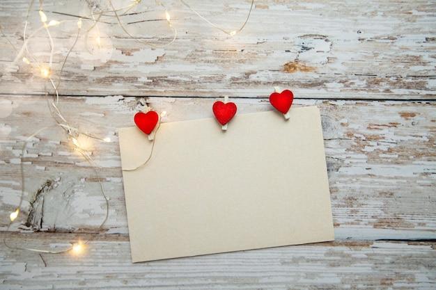 Cartão branco para texto com corações-prendedores de roupa vermelhos