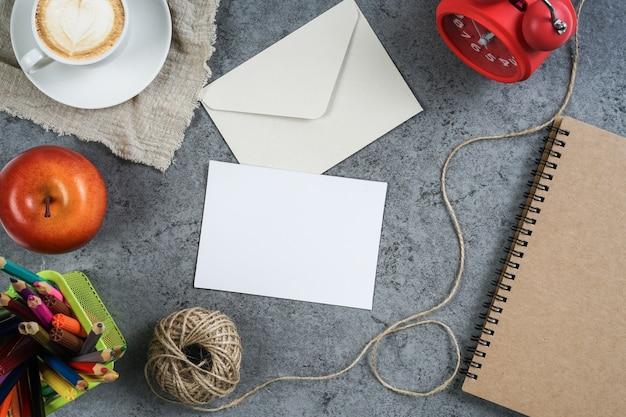Cartão branco vazio e envelope com rosca, maçã, despertador e lápis