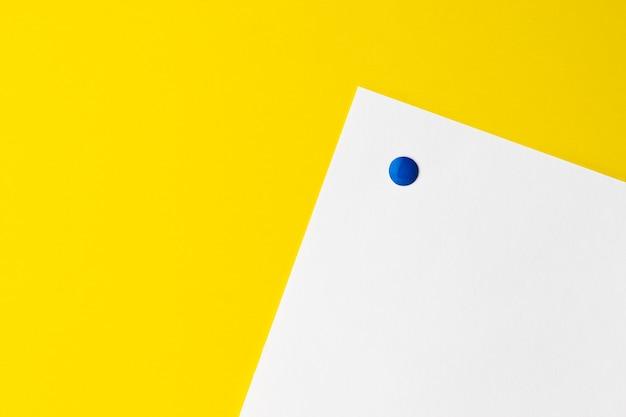 Cartão branco vazio é fixado ao fundo amarelo