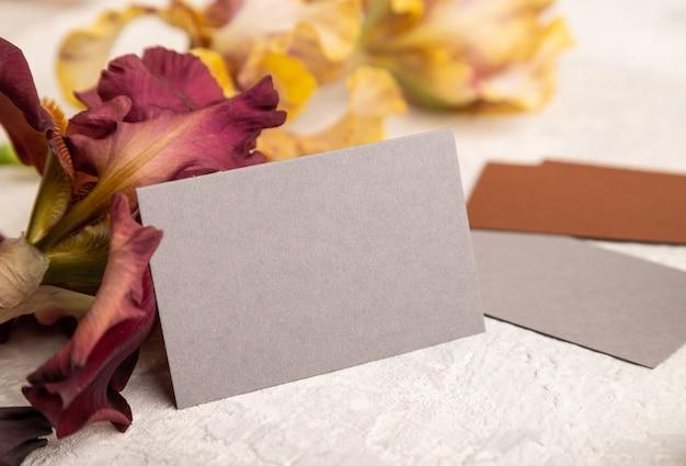 Cartão cinza com flores de íris em fundo cinza de concreto. vista lateral, cópia espaço, natureza morta.