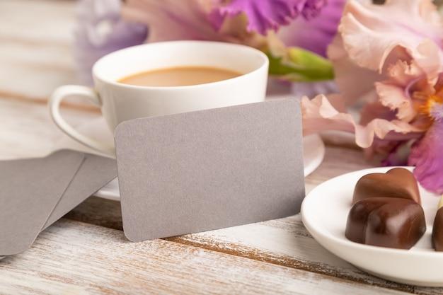 Cartão cinza com uma xícara de café, bombons de chocolate e flores de íris em fundo branco.