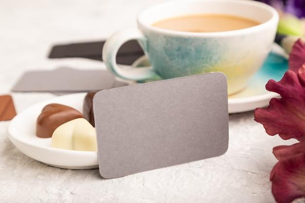 Cartão cinza com uma xícara de café, bombons de chocolate e flores de íris na superfície cinza.